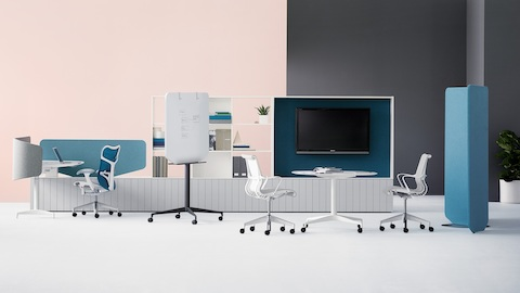 A Locale sit-to-stand workstation with a Blue Mirra 2 office chair near a collaborative meeting setting with gray fabric upholstered Setu chairs.