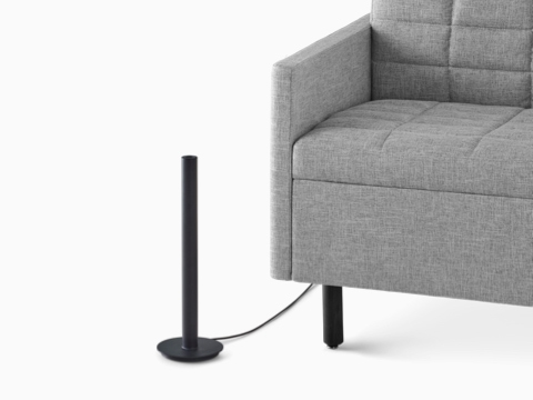 A black Logic Micro Tower placed next to a gray Tuxedo sofa.