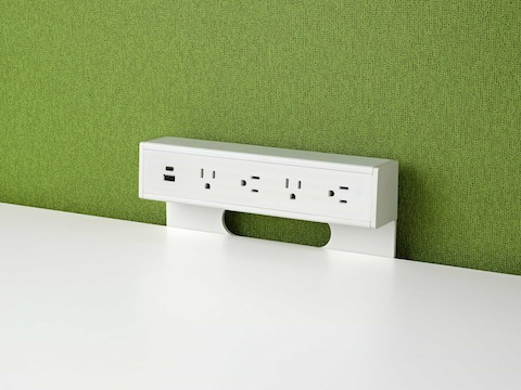 A white, surface-mounted Logic power port with four power outlets and two USB connections.