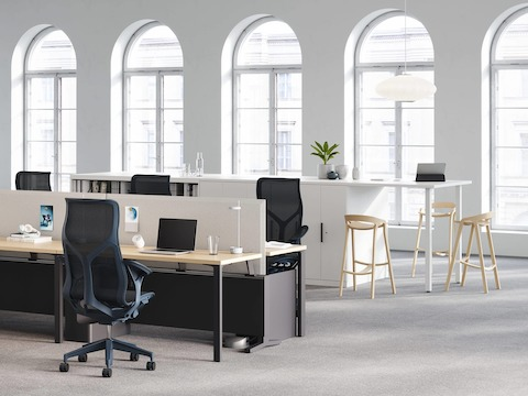 An open plan office with a Canvas Dock workstation acting as the power and data source for a round Logic Reach System Start. Four high-back Cosm office chairs are positioned at the workstation.
