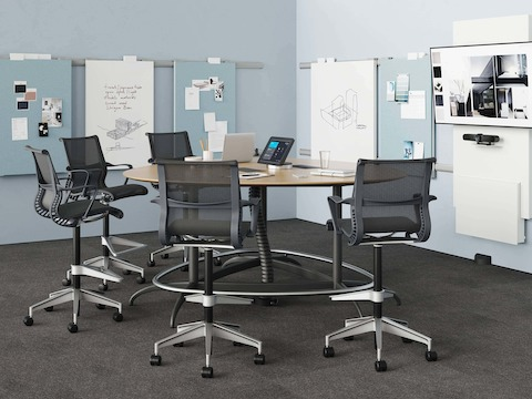 A meeting space featuring an Exclave table with five black Setu Stools. The table is connected to power and data by a Logic Reach Wall Start and Electrical Hub.