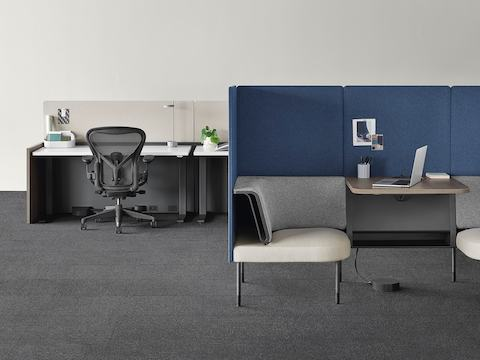An open plan office with a Public Social Chair in gray, blue, and light brown connected to power and data by a Logic Reach Electrical Hub, and a nearby black Aeron office chair and Canvas Channel workstation providing power and data to a Logic Reach System Start.