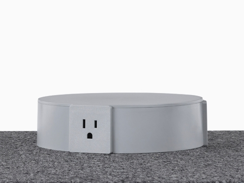 A close-up view of a light gray Logic Reach Electrical Hub sitting on carpet.
