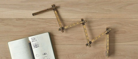 An overhead view of an antique folding ruler with a notebook and pencil on a wood surface.