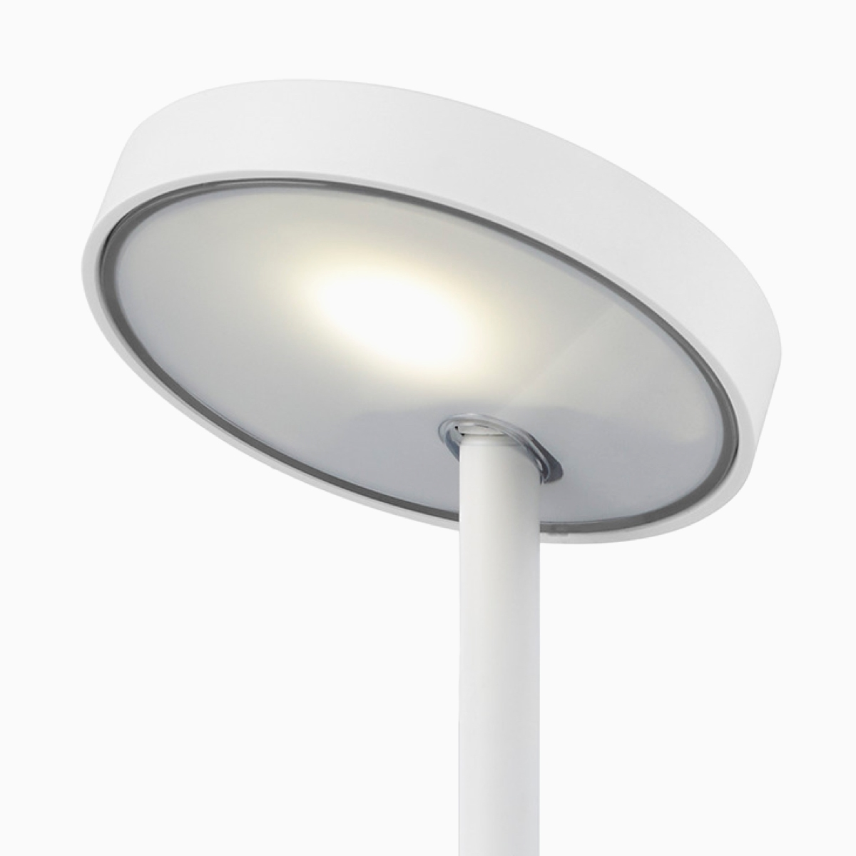 Three-quarter front view of Lolly Personal Light in white with the adjustable head tilted upward and the light on.