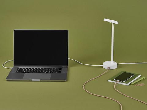 Lolly Personal Light in white with USB ports charging a phone and a laptop.