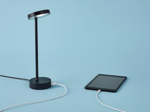 Three-quarter front view of the Lolly Personal Light in black with the adjustable head tilted up and a tablet plugged in to the USB port of Lolly.