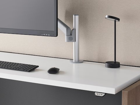 Three-quarter front view of a black Lolly Personal Light on a sit-to-stand desk with a neutral screen, grey Lima Monitor Arm, monitor, and keyboard.