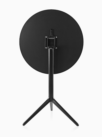 A black Magis Central occasional table with the round top folded down.