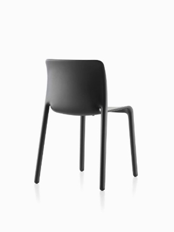 Three-quarter rear view of a black Magis Chair First plastic stacking chair.