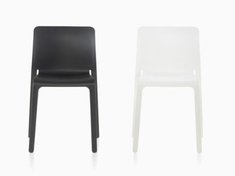 Side-by-side black and white Magis Chair First plastic stacking chairs, viewed from the front.