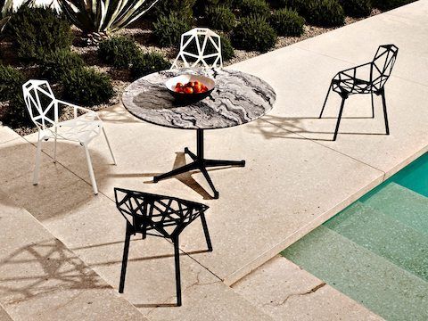 An outdoor view of Magis Chair_One side chairs used poolside, including versions with both white and black painted aluminum frames.