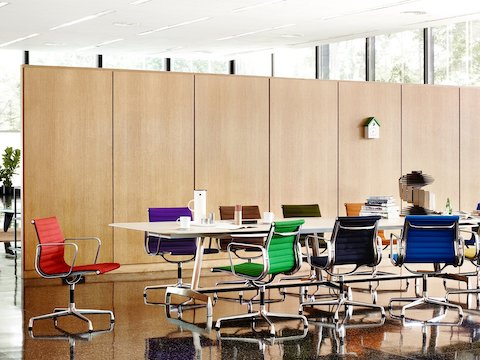 A Magis Cu-Clock with a green roof overlooks a meeting area featuring a rectangular table and Eames Aluminum Group Chairs.