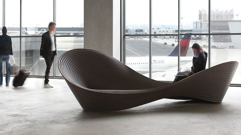 Brown Magis Folly Bench, viewed from front at angle in airport.