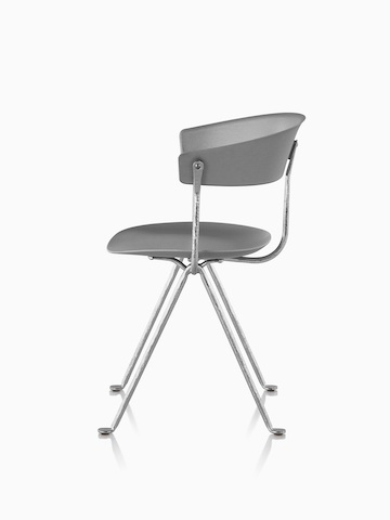 Profile view of a gray Magis Officina side chair with wrought iron legs.
