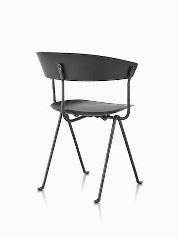 Three-quarter rear view of a black Magis Officina side chair with wrought iron legs.
