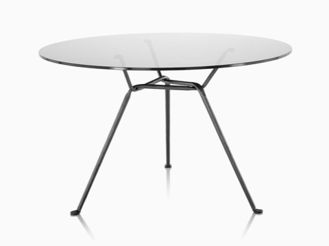 A round Magis Officina Table with a glass top and wrought iron legs.