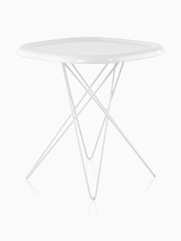 An angled view of a white Magis Pizza occasional table with steel rod legs and an oblong top reminiscent of a pizza.