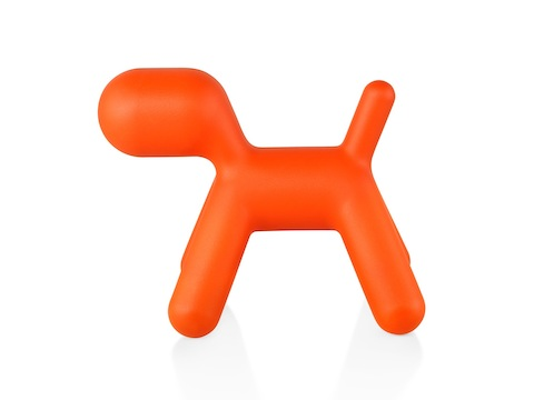 Profile view of an orange Magis Puppy, a sculptural plastic form shaped like an abstract dog.