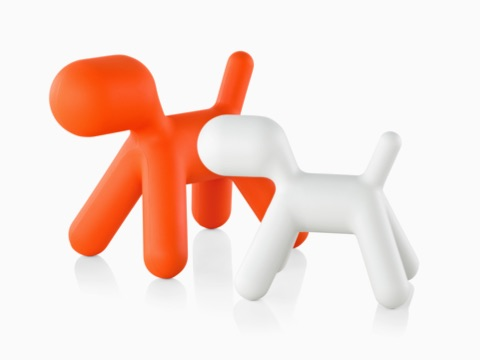 Orange and white versions of the Magis Puppy, a sculptural plastic form shaped like an abstract dog.
