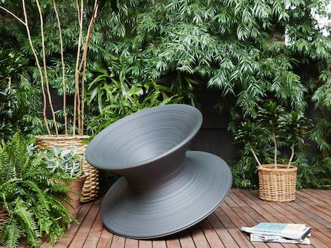 Gray Magis Spun Chair, viewed from side in casual setting.