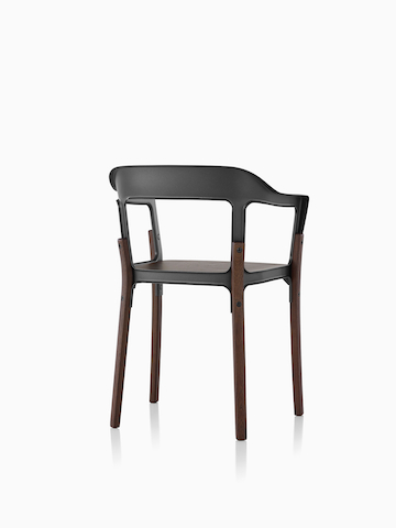 Angled view from behind a Magis Steelwood dining chair with black metal back and dark brown wooden legs.