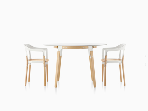 Two white Magis Steelwood side chairs on both sides of a round Magis Steelwood dining table.