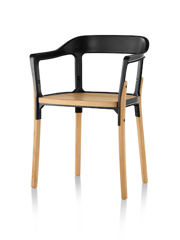 Angled view of the front of a Magis Steelwood side chair with black metal back and light brown wooden legs and seat.
