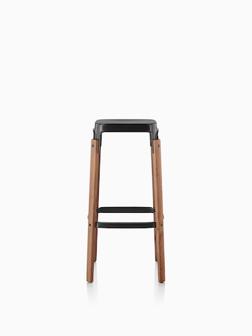 Magis Steelwood Stool with a black steel seat and wood legs.
