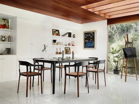 A rectangular Magis Steelwood Table with a black top and legs, surrounded by Magis Steelwood Chairs in a contemporary room.