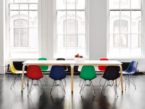 A rectangular Magis Steelwood Table with a white top, surrounded by Eames Molded Fiberglass Chairs in various colors.