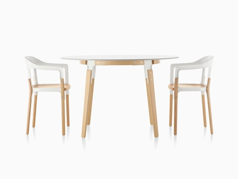 A round Magis Steelwood Table with a white top and wood legs in a light finish, paired with matching Magis Steelwood Chairs.