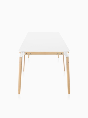 A rectangular Magis Steelwood Table with a white top and wood legs in a light finish, viewed from the narrow end.