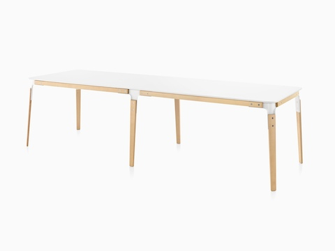 An angled view of a long rectangular Magis Steelwood Table with a white top and wood legs in a light finish.