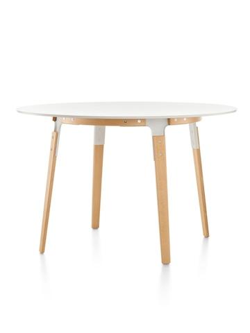 A round Magis Steelwood Table with a white top and wood legs in a light finish.