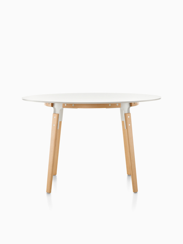 A round Magis Steelwood Table with a white top.