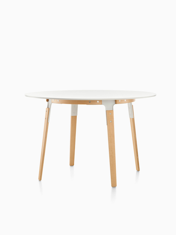A round Magis Steelwood Table with a white top. Select to go to the Magis Steelwood Tables product page.