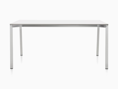 A partial view of a rectangular Magis Table_One table with a white top and polished aluminum legs.