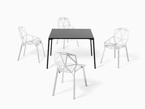 A black Magis Table_One Outdoor table with a square top, surrounded by four white Magis Chair_One side chairs.