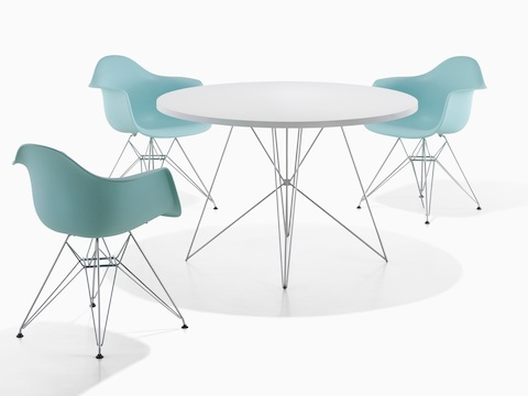 A round Magis Tavolo XZ3 Table with a white top, surrounded by three blue Eames Molded Plastic Chairs.