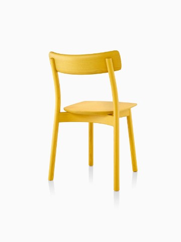 Three-quarter rear view of an armless Mattiazzi Chiaro stackable side chair with a yellow finish.