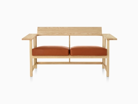 A Mattiazzi Clerici two-seat bench with orange cushions and a light wood finish, viewed from the front.