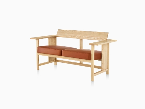 A Mattiazzi Clerici two-seat bench with orange cushions and a light wood finish, viewed from a 45-degree angle.