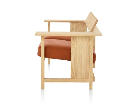 A Mattiazzi Clerici two-seat bench with orange cushions and a light wood finish, viewed from the side.