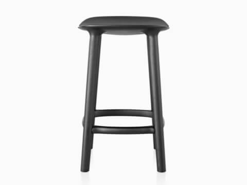 Profile view of a black Mattiazzi Osso wood stool.