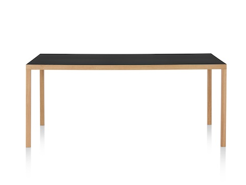 A rectangular Mattiazzi Primo Table with a black top and wood legs in a light finish, viewed from the long side.
