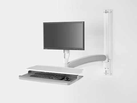 A computer monitor, keyboard, and small work surface supported by Mbrace Wall-Mounted Technology.
