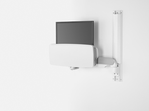 A computer monitor and folded keyboard tray supported by an Mbrace wall mount and positioned flush against the wall.