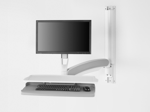 Partial view of a computer monitor, keyboard, and small work surface supported by Mbrace Wall-Mounted Technology.