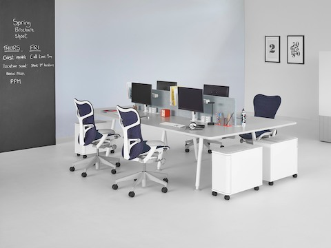 A white Memo project table with blue Mirra 2 office chairs.